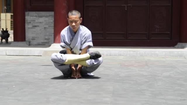a shaolin student demonstrates strength and flexibility. - カンフー点の映像素材/bロール