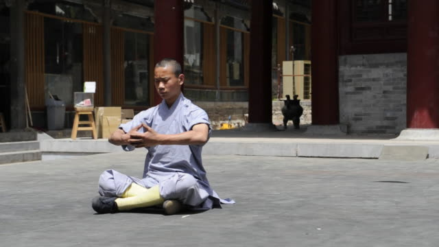a shaolin student twists his body into an unusual position as he demonstrates kung-fu flexibility. - カンフー点の映像素材/bロール