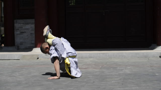 a shaolin student twists his body into unusual positions as he demonstrates flexibility. - flexibility stock videos & royalty-free footage