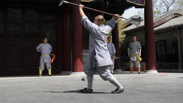 a shaolin student uses a weapon as he demonstrates a series of moves. - 少林寺点の映像素材/bロール
