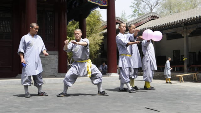 shaolin students assist a comrade as he breaks balloons to demonstrate a kung-fu skill. - 少林寺点の映像素材/bロール