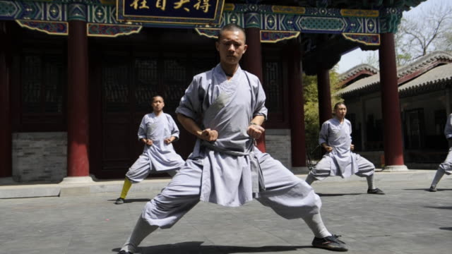 shaolin students move in unison as they demonstrate a martial arts routine. - カンフー点の映像素材/bロール