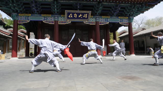 stockvideo's en b-roll-footage met shaolin students perform a choreographed kung-fu demonstration with weapons. - zwaard