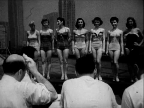 Shapely bare legs of women in bathing suits as they parade for the title of Swim for Heath Queen / faces of the women parading / photographers...