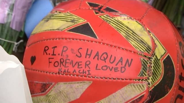 shaquan fearon murder trial: cctv footage shown in court; lib brockley: close shot of candles in front of photos and messages to shaquan football... - 飾り板点の映像素材/bロール