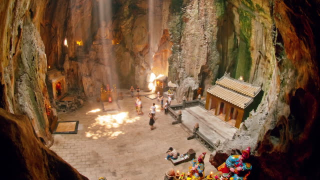 ms t/l shard of light and visitors to cave at marble mountain / da nang, vietnam - ダナン点の映像素材/bロール