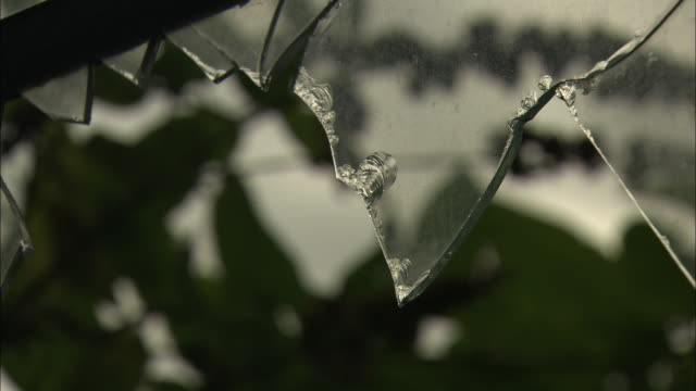 shards of glass hang from a window pane. - broken stock videos & royalty-free footage