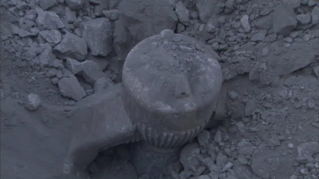 shards of rocks shudder as a huge drill bit moves beneath a rock pile. - ドリルビット点の映像素材/bロール