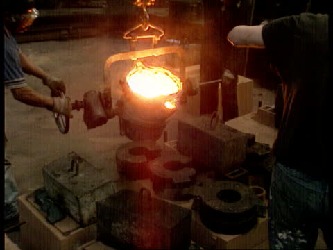 tms foundry worker pouring small vat of molten metal - foundry worker stock videos and b-roll footage