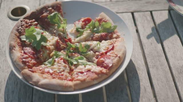 sharing pizza on plate in summer garden - plate stock videos & royalty-free footage