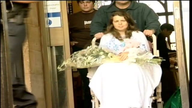jury discharged after failing to reach verdict on robbery charge tx pc milburn holding bouquet of flowers as wheeled from hospital in wheelchair - pc sharon beshenivsky stock videos & royalty-free footage