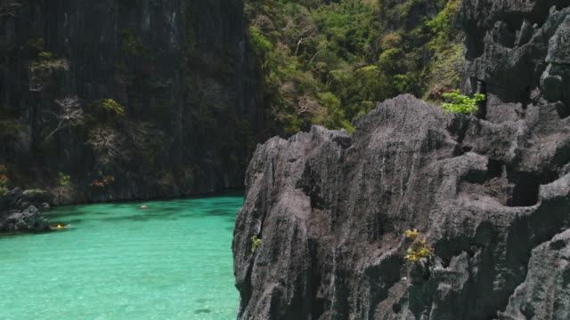 vidéos et rushes de murs de rocher pointu entourant la lagune isolée - philippines
