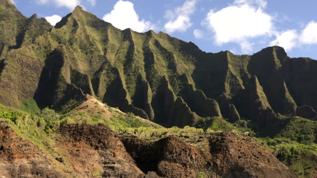 sharp spines of kauai island mountains in afternoon sunlight - butte rocky outcrop stock videos & royalty-free footage