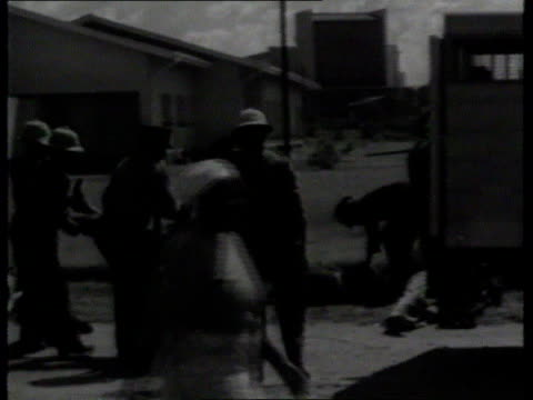 sharpeville massacre anniversary; sharpeville tms black man along past bodies of people killed by police r-l side body put on to lorry l-r wounded... - 大量殺人点の映像素材/bロール