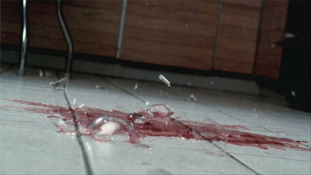 cu slo mo shattering wineglass on floor / san francisco, california, usa - bicchiere da vino video stock e b–roll