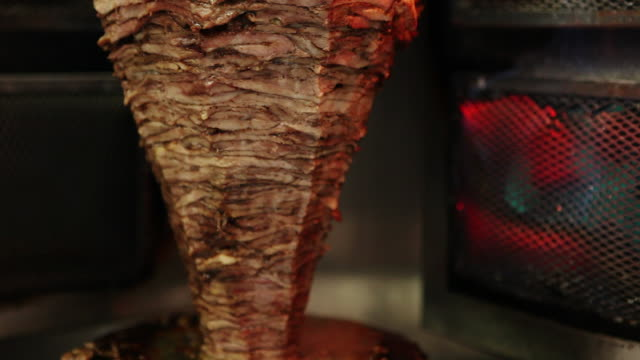 a shawarma spins next to a fire. - kebab stock videos and b-roll footage