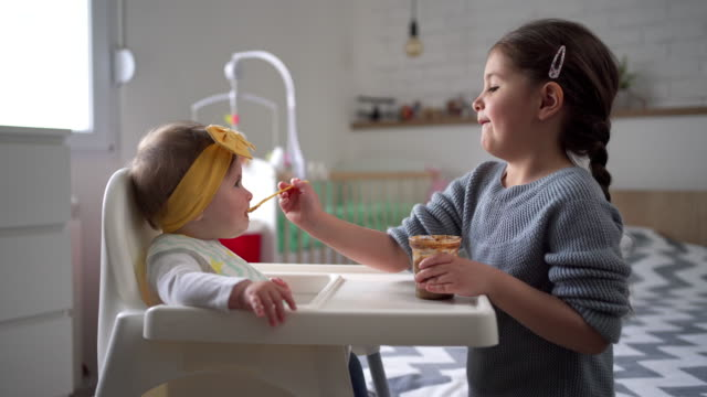 she always take care of her baby sister and she loves to feed her in the morning - sibling stock videos & royalty-free footage