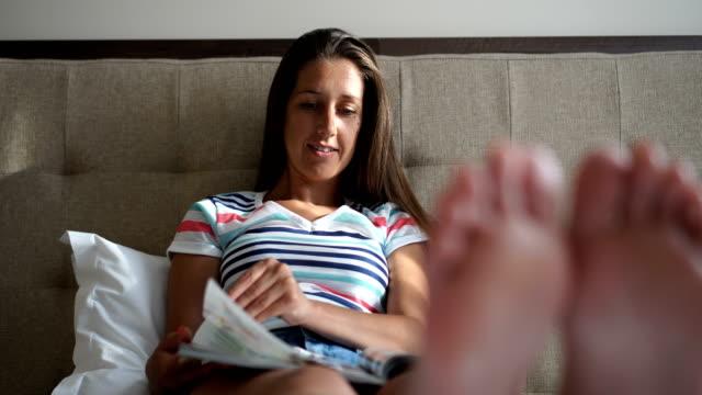 sie genießt zu hause, lesen zeitschriften - magazine stock-videos und b-roll-filmmaterial