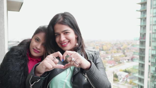 vídeos de stock, filmes e b-roll de ela é a única! - meninas que fazem a forma do coração usando as mãos - idade humana
