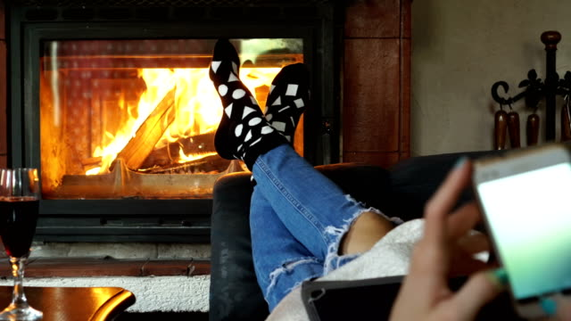 she use mobile phone while she relax her feet near fireplace - sock stock videos & royalty-free footage