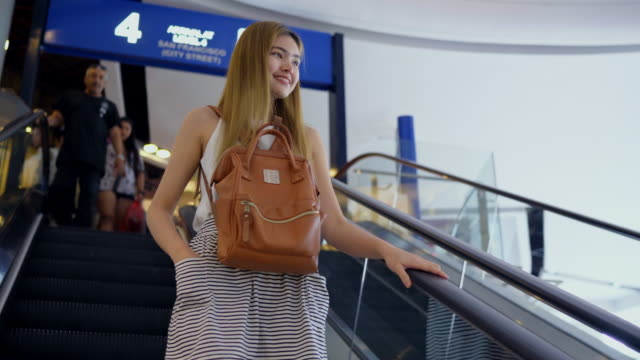 she walk down the escalator, she smiled happily In the airport.