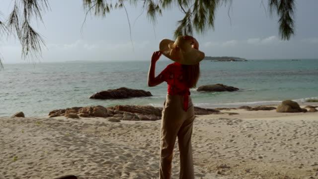 彼女は木の床で海帽子立っているを着用し、彼女は笑顔で、夕暮れ時に何かを探します。 - 帽子点の映像素材/bロール