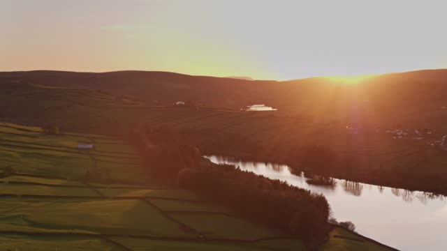 Sheep Grazing Land Leading Down to Reservoir in Yorkshire at Sunset - Drone Shot