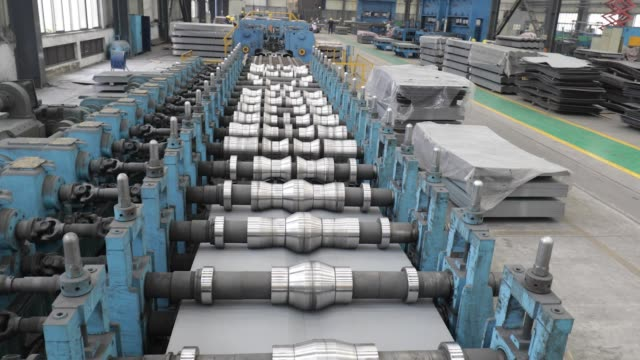 a sheet of metal is pressed along rollers creating corrugation in the metal pressing shop at the singamascontainer holdings ltd factory in qidong... - sheet metal stock videos and b-roll footage
