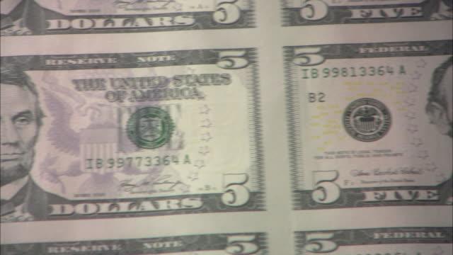 vídeos de stock e filmes b-roll de pan sheet of newly-printed and uncut five dollar bills / washington, district of columbia, united states - nota de cinco dólares dos estados unidos