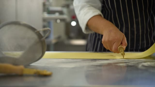 sheet of pasta is cut in half - pasta machine stock videos and b-roll footage