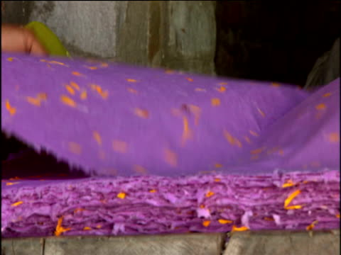 Sheet of purple fabric with gold decoration being laid on pile on market stall Jaipur
