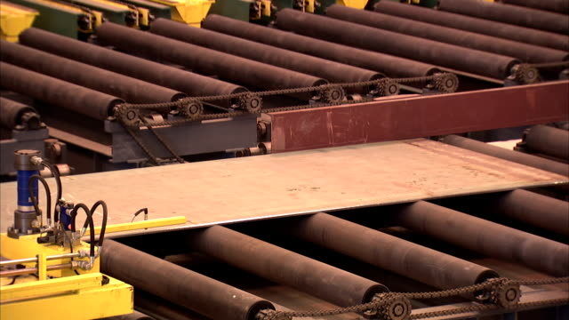 a sheet of steel moves across rollers. - industria metallurgica video stock e b–roll