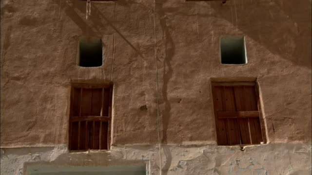 sheets cover windows on a mud brick high rise building in shibam yemen. - yemen stock videos and b-roll footage