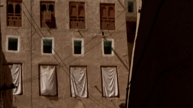 Sheets cover windows on a mud brick high rise in Shibam Yemen.