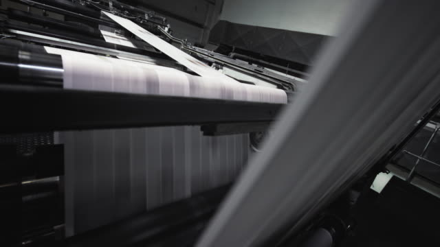 vídeos de stock e filmes b-roll de sheets of paper running across the rolls of the printing press - jornal