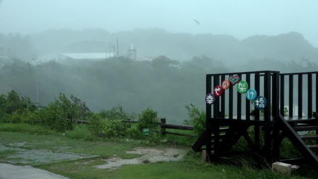 Sheets of rain sweep against hillside as powerful hurricane force winds as typhoon Trami hits Okinawa Japan