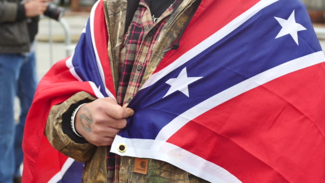 vídeos de stock e filmes b-roll de a man wraps himself in a confederate flag as white nationalist groups gather for a white lives matter rally in downtown shelbyville tennessee the... - comício político
