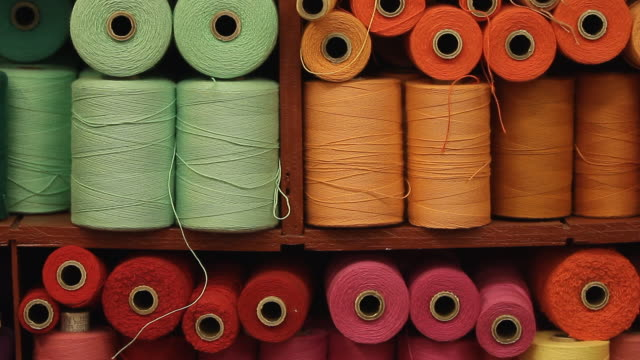 a shelf full of colorful spools of thread - ball of wool stock videos & royalty-free footage