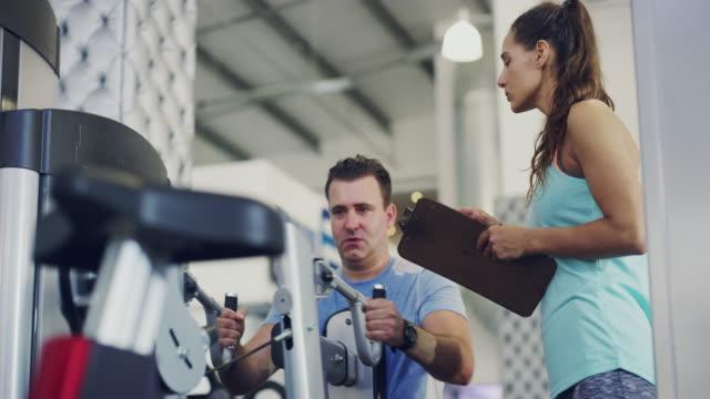 vídeos de stock, filmes e b-roll de ela vai ajudá-lo a entrar em forma - instrutor de fitness