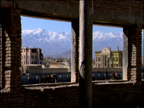 Shelled municipal buildings with snow capped mountains in distance seen from ruins following fall of Taliban Kabul; 2002