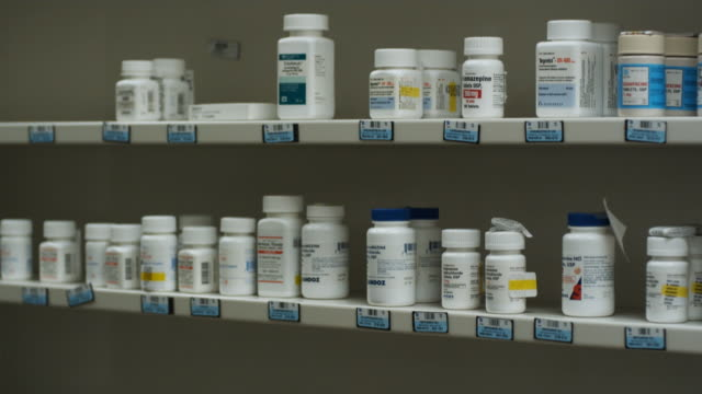 shelves of drugs at pharmacy - prescription medicine stock-videos und b-roll-filmmaterial