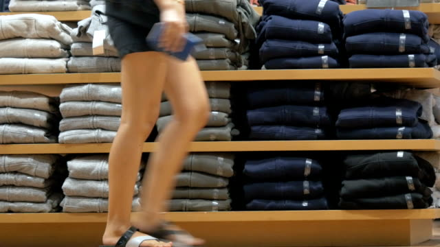 vídeos de stock e filmes b-roll de shelves with clothes in retail store - jeans