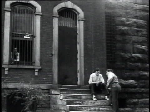ws sheriff sits on the steps of a jail from which dillinger escaped / indiana united states - john dillinger stock-videos und b-roll-filmmaterial
