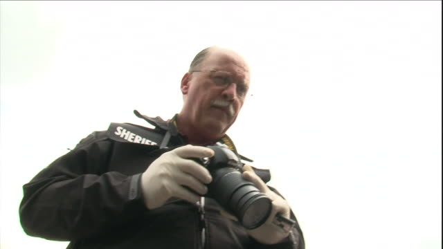 a sheriff takes pictures at a crime scene. - plastic bag stock videos & royalty-free footage