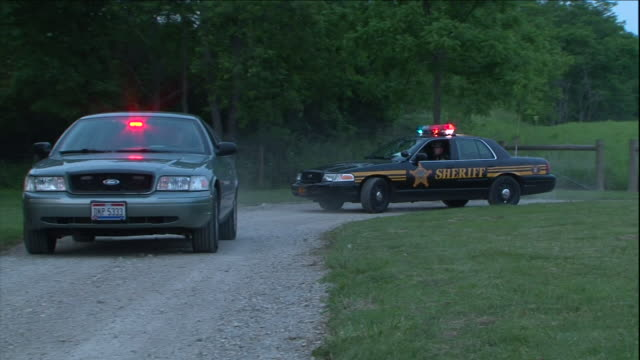 """a sheriff'""""s car and a police cruiser with flashing lights drive along a dirt road in the country. - police car stock videos & royalty-free footage"""