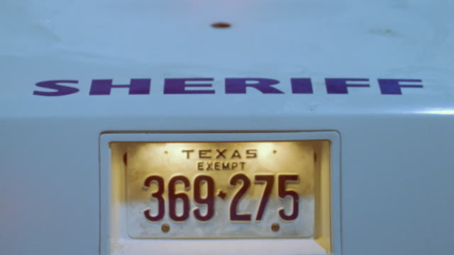 a sheriff's car with a texas license plate pulls out of an intersection with the light bar flashing. - texas stock videos & royalty-free footage