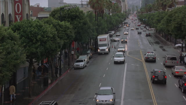 A Sheriff's Department buss travels down a busy Los Angeles street escorted by a police car in this following shot.
