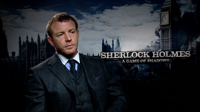 vídeos de stock e filmes b-roll de game of shadows': cast interviews; england: london: int guy ritchie interview sot - on not being surprised with the audience wanting more from him... - stephen fry