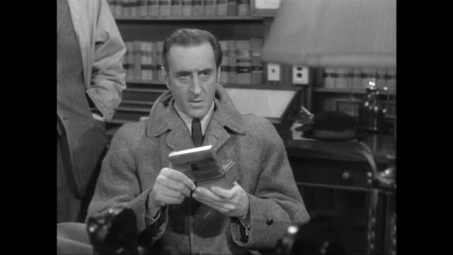 1946 sherlock holmes (basil rathbone) and doctor watson (nigel bruce) try to determine music box significance - trillerpfeife stock-videos und b-roll-filmmaterial