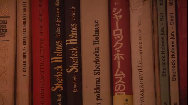 sherlock holmes books, written by sir arthur conan doyle, line a bookshelf. - sherlock holmes stock videos & royalty-free footage